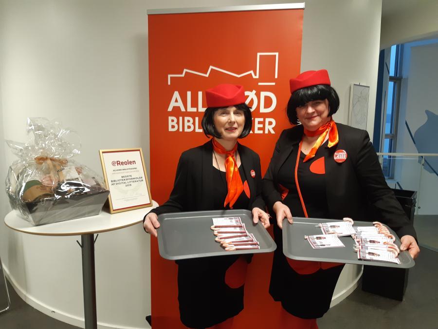 Bogstewardesser i fuld uniform med prikkede kjoler uddeler Allerød Biblioteks efterårsprogram